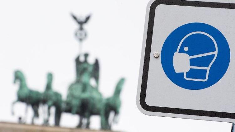 Am Pariser Platz weist ein Hinweisschild auf die Maskenpflicht hin. Foto: Christophe Gateau/dpa/Symbolbild