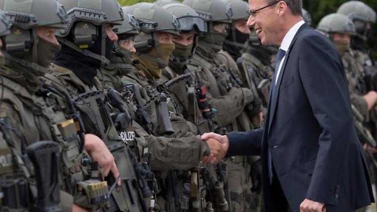Innenminister Peter Beuth (CDU) mit Beamten des Spezialeinsatzkommandos (SEK) der Polizei Frankfurt. Foto: Boris Roessler/dpa/Archivbild