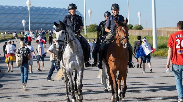 Polizeibeamte der Reiterstaffel patroullieren vor dem Stadion durch die ankommenden Fans. Foto: Matthias Balk/dpa