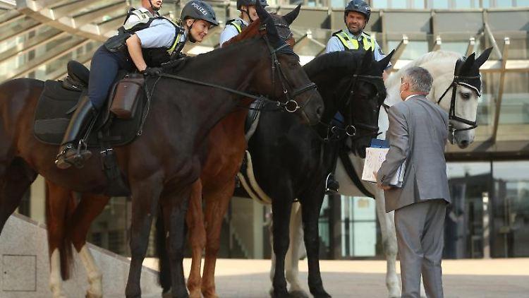 Der nordrhein-westfälische Innenminister Herbert Reul (rC, DU) spricht am Landtag mit der Polizei. Foto: David Young/dpa