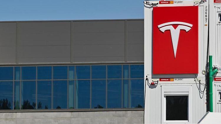 Das Logo von Tesla hängt an einem Container auf der Baustelle der Gigafactory. Foto: Patrick Pleul/dpa-Zentralbild/ZB/Archivbild