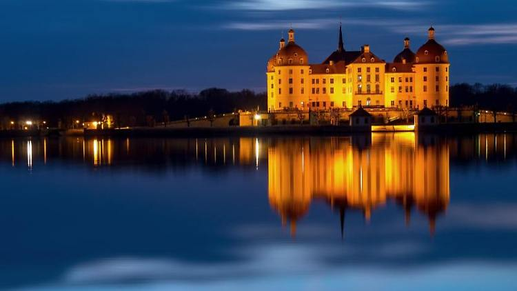 Das beleuchtete Schloss Moritzburg spiegelt sich am Abend im Schlossteich. Foto: Monika Skolimowska/ZB/dpa/Archivbild