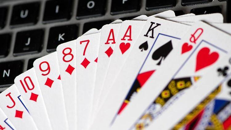 Spielkarten liegen auf der Tastatur eines Notebooks. Foto: Axel Heimken/dpa/Symbolbild