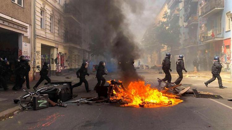 Polizisten laufen auf der Rigaer Straße an einer brennenden Barrikade vorbei. Foto: Andreas Rabenstein/dpa