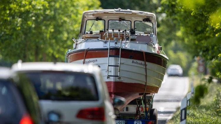 Ein Motorboot wird auf einem Bootsanhänger durch eine Allee Richtung Ostsee transportiert. Foto: Jens Büttner/dpa-Zentralbild/dpa/Archivbild