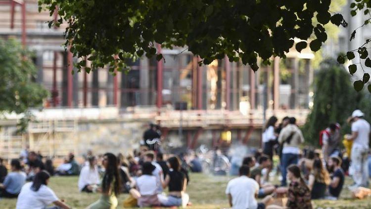 Menschen sitzen abends bei schönem Wetter im James-Simon-Park. Foto: Kira Hofmann/dpa-Zentralbild/dpa/Archivbild