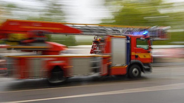Ein Feuerwehrfahrzeug mit Drehleiter fährt zu einem Einsatz. Foto: Robert Michael/dpa-Zentralbild/ZB/Symbolbild