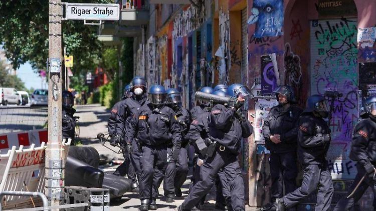 Polizisten gehen mit einem Rammbock vorbei an einer Barrikade in die Rigaer Straße. Foto: Jörg Carstensen/dpa/Archivbild