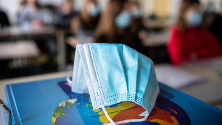 EinMund-Nasen-Schutz liegt während des Unterrichts auf einem Atlas. Foto: Matthias Balk/dpa/Illustration