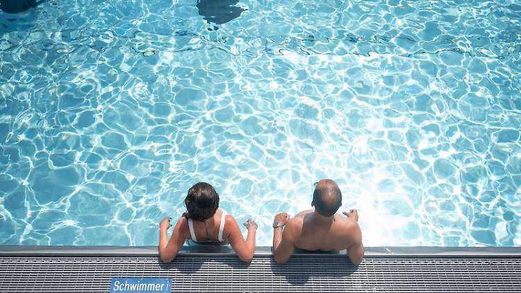 Zwei Badegäste stehen in einem Schwimmbecken. Foto: Sebastian Gollnow/dpa/Archivbild