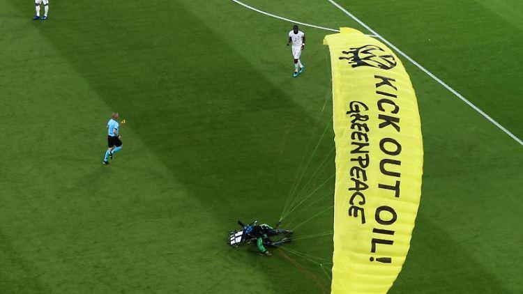 Ein Greenpeace-Aktivist landet auf dem Spielfeld. Foto: Christian Charisius/dpa/archivbild