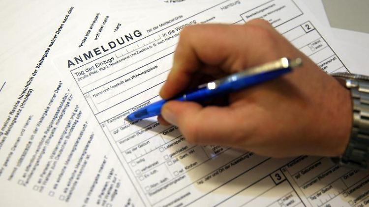 Meldeunterlagen für das Einwohnermeldeamt liegen auf einem Tisch. Foto: picture alliance / dpa/Illustration