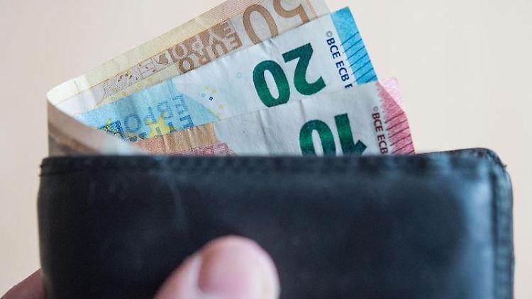 Geldscheine stecken in einem Geldbeutel. Foto: Lino Mirgeler/dpa/Illustration