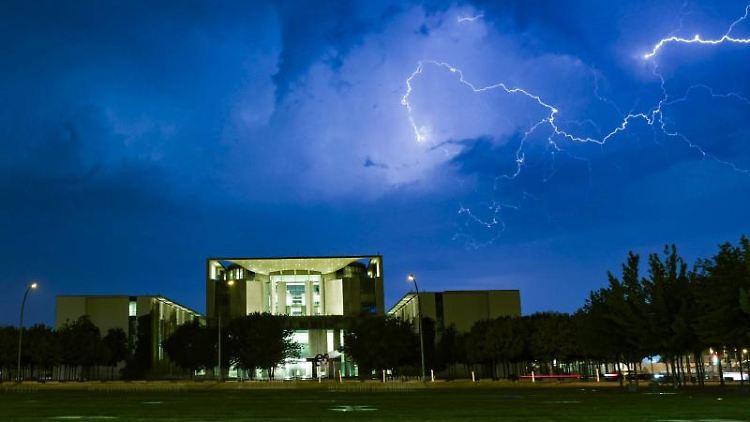 Blitze zucken während eines Gewitters über dem Bundeskanzleramt über den Himmel. Foto: Paul Zinken/dpa/Archivbild