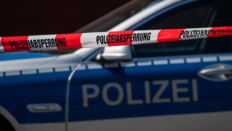 Ein Polizeiauto steht hinter einem Absperrband der Polizei. Foto: Robert Michael/dpa-Zentralbild/dpa