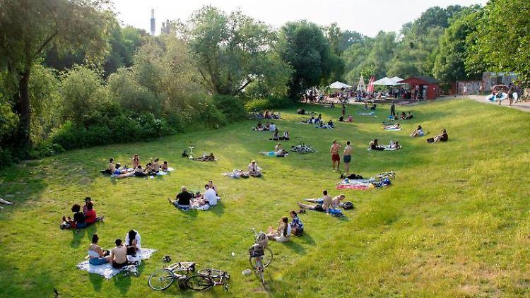 Zahlreiche Menschen sitzen am Ufer der Ihme. Foto: Hauke-Christian Dittrich/dpa/Archivbild