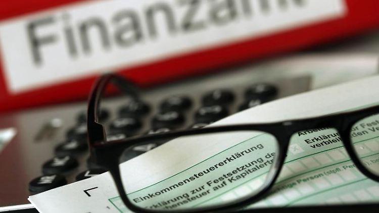 ARCHIV - ILLUSTRATION - Auf einem Vordruck für die Steuererklärung liegt am 20.11.2013 vor dem Aktenordner mit dem Aufdruck