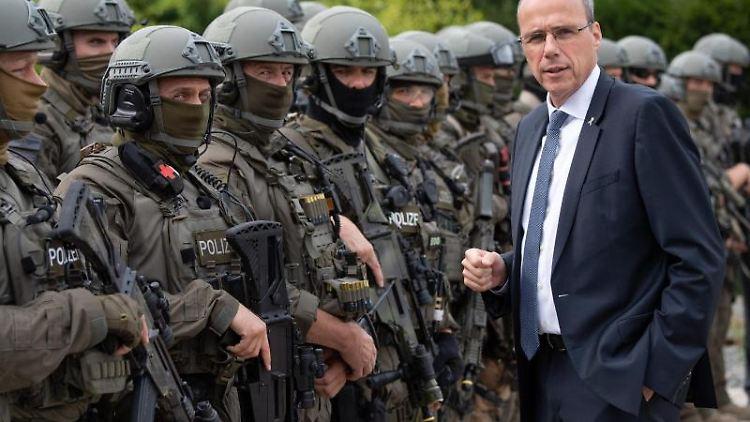 Der hessische Innenminister Peter Beuth (r, CDU) spricht am Rande einer SEK-Übung. Foto: Boris Roessler/dpa/Archivbild