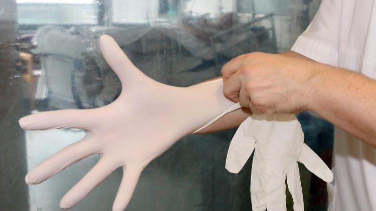Ein Pfleger auf der Intensivstation in einem Krankenhaus zieht sich Handschuhe an. Foto: Stephanie Pilick/dpa/Archivbild