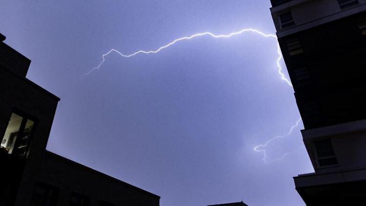Ein Blitz hellt zwischen einer Häuserfassade auf. Foto: Marcel Kusch/dpa/Archivbild