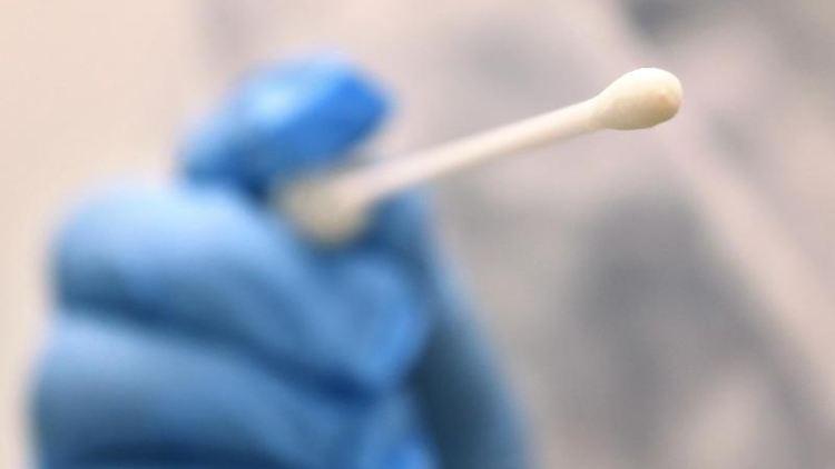 Eine Hand hält Tupfer, mit dem ein Abstrich für einen Corona-Test gemacht wird. Foto: Karl-Josef Hildenbrand/dpa/Symbolbild