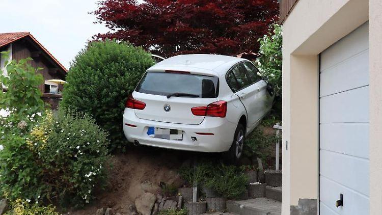 Das Auto einer Fahranfängerin hängt nach einem Unfall imVorgarten eines Hauses. Foto: A.Hartl/zema-medien.de/dpa