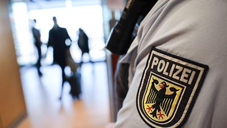 Ein Beamter der Bundespolizei kontrolliert Reisende am Flughafen. Foto: Christian Charisius/dpa/Symbolbild