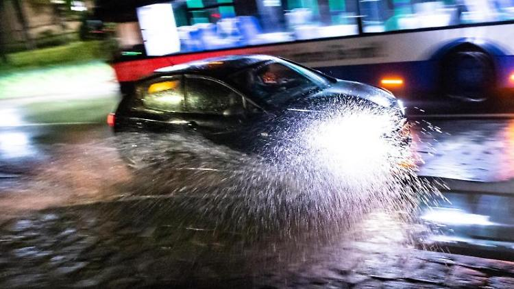 Ein Auto fährt durch eine Unterführung, die nach einem Hitzegewitter überschwemmt ist. Foto: Matthias Balk/dpa