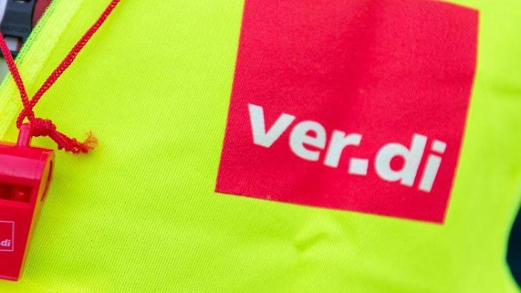 Ein Streikender trägt eine Warnweste mit dem Verdi-Logo und eine rote Trillerpfeife. Foto: Christophe Gateau/dpa/Symbolbild