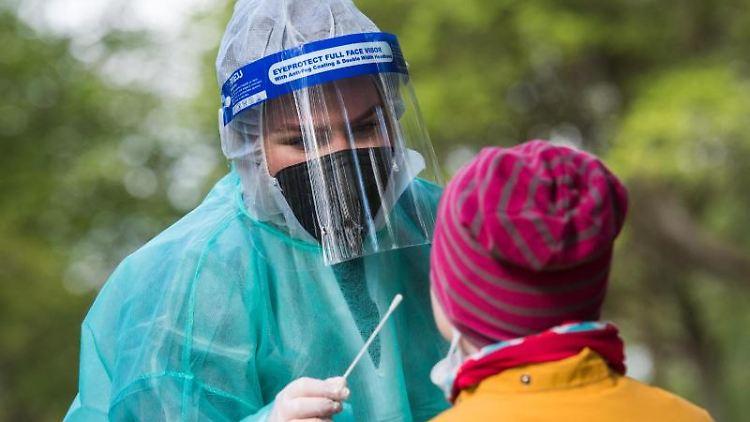 Eine Mitarbeiterin in einem Corona-Testzentrum macht bei einem Mädchen einen Corona-Test. Foto: Daniel Bockwoldt/dpa/Archivbild