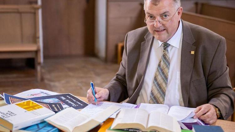 Pfarrer Claus Ebeling arbeitet an einer Mundart-Bibel auf Fränkisch. Foto: Daniel Karmann/dpa