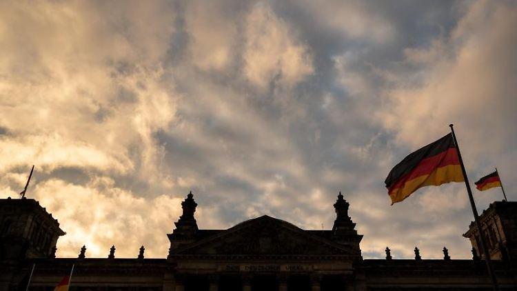 Bei Sonnenaufgang ziehen Wolken über das Reichstagsgebäude. Foto: Christophe Gateau/dpa/Symbolbild