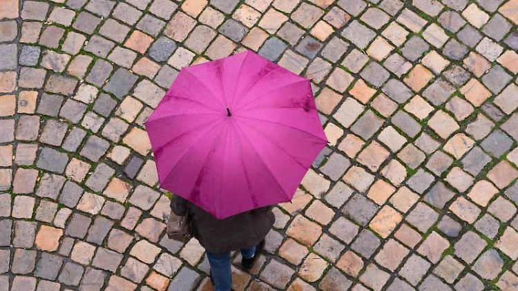 Eine Frau geht mit einem Regenschirm auf einer Straße entlang. Foto: Sebastian Kahnert/dpa-Zentralbild/dpa/Symbolbild