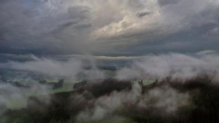 Nebelschwaden ziehen durch die wolkenverhangene Allgäuer Landschaft. Foto: Karl-Josef Hildenbrand/dpa