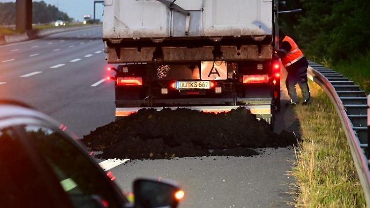 Ein Laster, der auf der A57 Klärschlamm verloren hat, steht auf dem Seitenstreifen. Foto: Alex Forstreuter/dpa