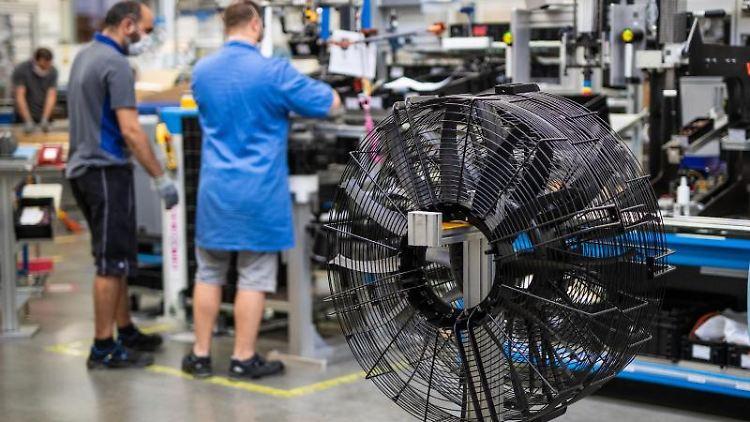 Mitarbeiter von EBM-Papst arbeiten an einem Ventilator. Foto: Christoph Schmidt/dpa