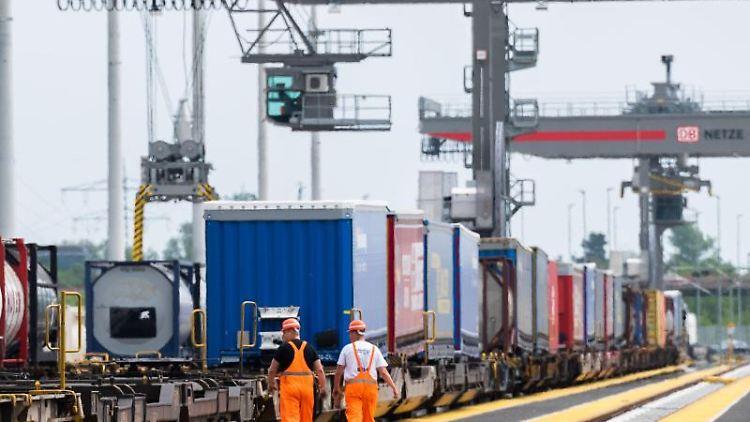 Mitarbeiter laufen am Containerbahnhof MegaHub. Foto: Julian Stratenschulte/dpa