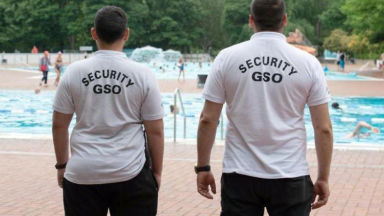 Mitarbeiter eines Sicherheitsdienstes stehen am Beckenrand eines Freibads. Foto: Paul Zinken/dpa-Zentralbild/dpa