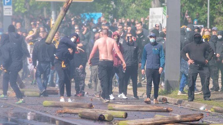 Fans von Dynamo Dresden werfen Holzpfähle in Richtung der Polizei. Foto: Sebastian Kahnert/dpa/Archivbild