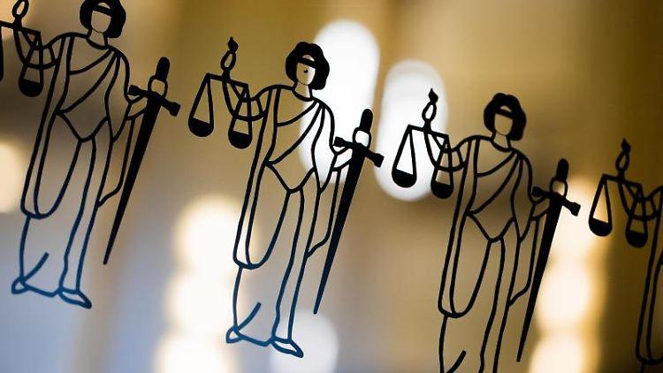 Abbildungen der Justitia an einer Scheibe am Eingang zu einem Gericht. Foto: Rolf Vennenbernd/dpa/Symbolbild