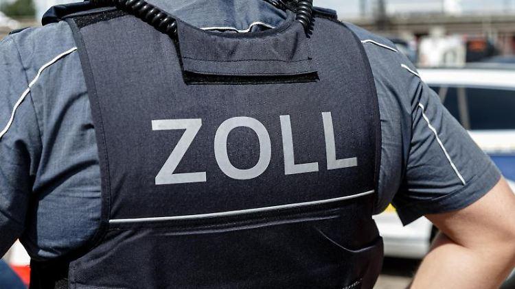 Ein Beamter trägt eine Schutzweste mit der Rückenaufschrift