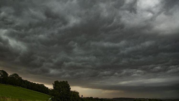 Dunkle Gewitterwolken sind am Nachthimmel über einer Wiese zu sehen. Foto: Tobias Hartl/vifogra/dpa