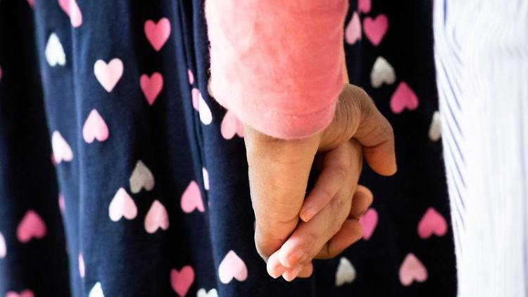 Hand in Hand tanzen Kinder und Erzieherinnen bei einem Bewegungsspiel. Foto: Christian Charisius/dpa/Symbolbild