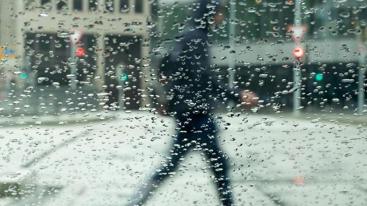 Regentropfen sammeln sich auf einer Autscheibe an der ein Mann vorbeigeht. Foto: Bernd Weißbrod/dpa/Archivbild