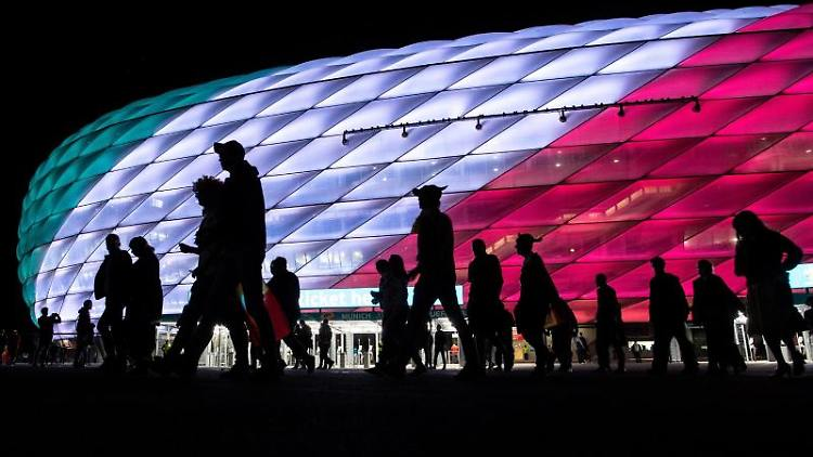 Fans verlassen nach dem Spiel das Stadion, das in den Farben der Landesflagge von Italien leuchtet. Foto: Matthias Balk/dpa