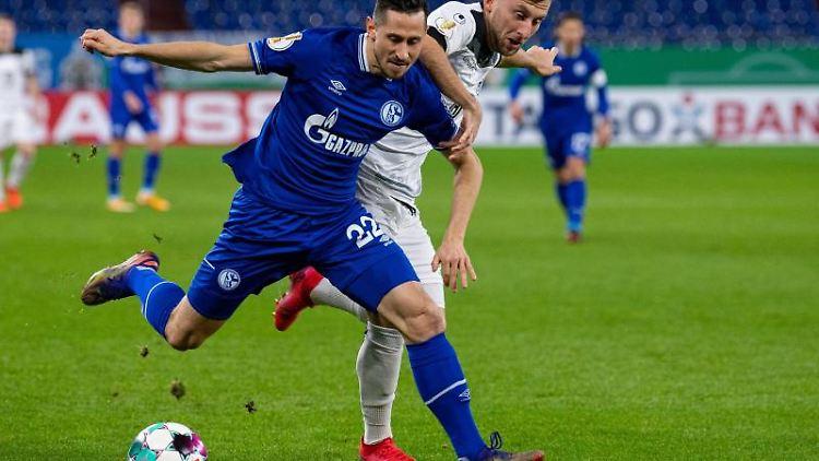 Schalkes Steven Skrzybski (l) und Ulms Albano Gashi kämpfen um den Ball. Foto: Guido Kirchner/dpa/Archivbild