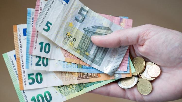 Eine Frau hält Geldscheine und Münzen in der Hand. Foto: Daniel Karmann/dpa/Symbolbild
