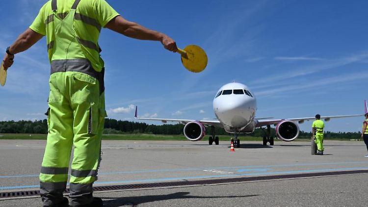 Ein Mitarbeiter des Bodensee-Airports weist das Passagierflugzeug zu seinem Platz. Foto: Felix Kästle/dpa