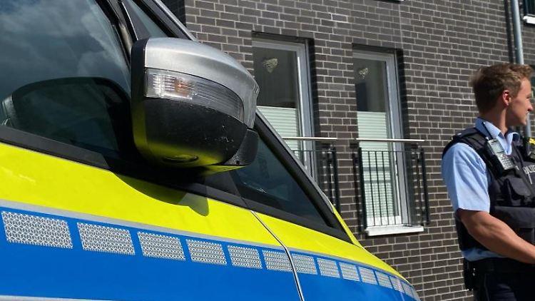 Ein bewaffneter Polizeibeamter steht in der Nähe eines Wohnhauses. Foto: Tim Oelbermann/dpa