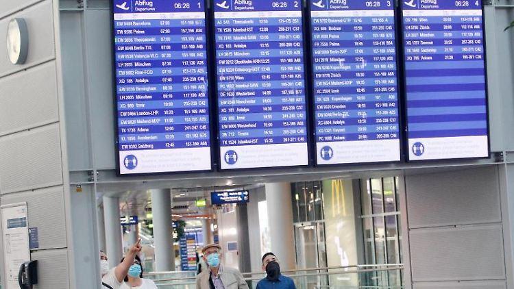 Fluggäste mit Masken schauen am Düsseldorfer Flughafen auf Informationstafeln mit Abflugzeiten. Foto: Roland Weihrauch/dpa/Archivbild